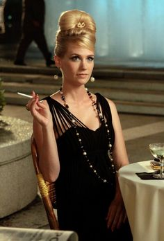 January Jones's character, Betty Draper, slowly started to change her style during season 3, set in 1963, from the stay-at-home mom outfits with flared skirts and button down tops to a more sexy style with big earrings and a long necklace.