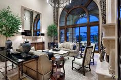 Living Room An Amazing Mediterranian Living Room With Arched Window And Grey Comfort Sofa With Antique Table And Glamorous Large Mirror Decor And Indoor Potted Plant Decors How to Put the Most Exciting and Exotic Houseplant in Green Living Room