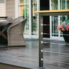 A perfect blend of modern and industrial elements in this deck railing. Cable ties on a metal framework topped with a reclaimed wood handrai