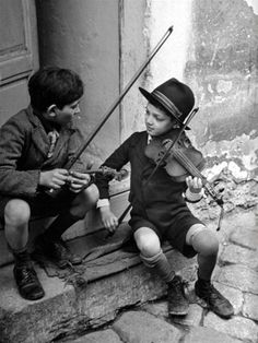 Gypsy children playing violin in street, Budapest, Hungary, 1939 / N.R. Farbman.