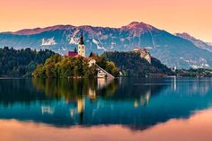 The small town of Bled stands proudly in front of the Julian Alps in Slovenia. Visit Slovenia, Bled Slovenia, Slovenia Travel, Peles Castle, Julian Alps, Small Towns, Cool Places To Visit, The Good Place, Santorini