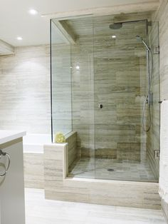 The owners borrowed space from the bedroom closet to allow for a soaker tub and separate shower. Showstopping Ocean Blue travertine from Saltillo Imports adds texture and warmth. The tile continues fr