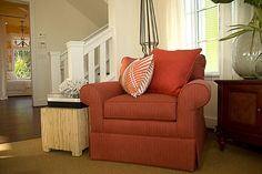 The furnishings are mainly coral rose in color, including the sofa and matching armchairs.