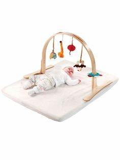 This Lilliputiens Ecodoux Wooden Activity Arch is long on stimulating play and short on environmental impact. The adjustable wooden arch holds four, detachable, hanging toys: a panda rattle, a crinkle flower with peek-a-boo mirror, a magic lantern rattle, and a terrific tiger with a hidden magnet. This sleek, hypoallergenic, eco-friendly activity toy is designed to develop baby's senses while appealing to parent's design sensibilities. Measures 23.5 x 20 inches.