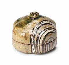 An Oribe Kogo [Incense Box] Edo period (17th-18th century) Of lobed form, the cover with a small finial, decorated in green Oribe glaze with a geometric design of three lines in iron black and white glazes, with shifuku [carrying pouch] and wood box 6.2cm. wide