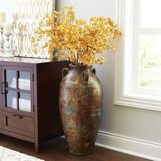 Inspired by the palace-style <i>amphorae</i> used to transport wine and dry goods in ancient Greece, our three-handled floor vase delivers classical grandeur to your living room or entryway. In addition to its striking silhouette, it features subtle linear carving and a distressed, hand-painted patina—a grand solution for showing off dried florals.