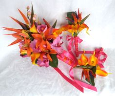 Tropical wedding bridal bouquet matching boutonnieres bright orange fuchsia pink tropical bouquets. $215.00, via Etsy.
