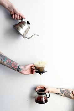 Pour over coffee brewing method process - 15-02-2016, Kiev, Ukraine, Pour over coffee brewing method process by barista with tattoos in natural light an wooden background