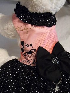 One of my favorite Disney caricatures is Mickey Mouse and I love finding fabric I can use in creating my pet outfits. The top is cotton and lined with cotton for comfort. Skirt is also cotton in black with tiny white dots also lined. The collar is made of same fabric and gathered around the neckline with a ruffle look. Black fabric bow at waist with black and white button and a d-ring right below the bow. Velcro closures at neck and waist that will adjust for comfort. The pretty little girl…
