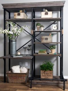 A heavy wood-and-metal shelf unit merges vintage and industrial touches while neutral tones and flowers help add a feminine vibe to the room.