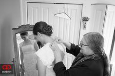 Elizabeth + Patrick's Wedding at Lenora's Legacy. Photo credit: Cureton Photography Mom helps bride into dress.