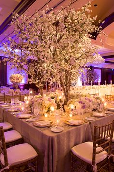 Table with Cherry Blossom Tree & Ivory, Pastel Purple & Mint Flowers Photography: Jay Lawrence Goldman Photography Read More: http://www.insideweddings.com/weddings/elegant-white-lavender-ballroom-wedding-with-cherry-blossom-trees/710/