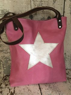 "Pink tote with a silver star! Sturdy pink cowhide tote measures 13"" wide by 14"" tall and 2"" deep. Brown cowhide straps are rivited on with antique brass rivets and have a drop of 11"". Cotton canvas upholstery fabric lining coordinates perfectly and has two slip pockets. Fastens with a magnetic snap. All leather."