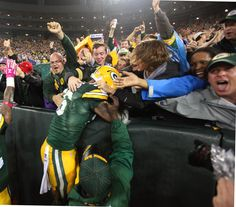 Green Bay Packers outside linebacker Julius Peppers does a Lambeau Leap after his INT return. - Image credit: Rick Wood