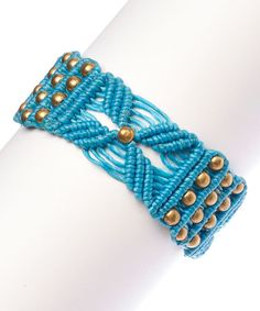 Metallic studs bring modern detail to this intricate bracelet showcasing woven strands of waxed cotton.
