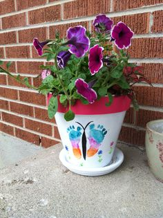 DIY flower pots with baby foot butterfly. I mod podged a photo of our baby to the back and wrote her name with the year. It makes a great gift I used this one for Mother's Day . I suggest using two people when painting your child's foot and applying it to the pot mine was whining and kicking .