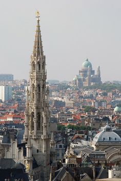Photo taken from the terrace on the 10th floor of the musical instruments museum in Brussels. The architectural style of the town hall is an example of flamboyant Gothic. The building is atop its 96 -meter tower topped with a gilded statue of the archangel Michael who fells a dragon . Basilica of Koekelberg: the National Basilica of the Sacred Heart in Koekelberg was built between 1905 and 1970. The final draft was designed by the Ghent architect Albert Van Huffel .