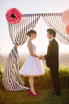 black and white stripe curtains and large pink paper flowers as modern and whimsical wedding ceremony decor | photo: www.daniellecapitophotography.com