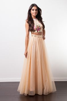 Pinkly smiling tanned lady in waistlength chocolate hair, cream sleeveless floral crop, blush pleated tulle maxi
