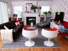This red and white eclectic living room features a bold patterned wallpaper, custom fireplace with built-ins and vintage midcentury modern chairs.