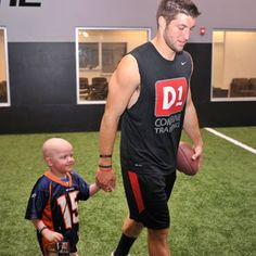 Tim Tebow holding the hands of a brave boy who is fan of Tbow. He melts my heart