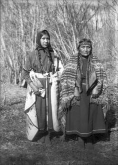 Aggie and Angeline, two Native American (Sioux) women stand in front of trees with bare branches in Montana.