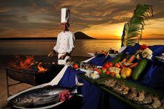 Koch des Siladen Resorts in Indonesien bereitet BBQ am Strand zu.