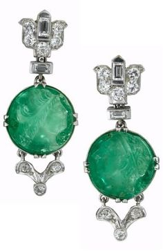Art Deco platinum, carved emerald and diamond earrings, attributed to Mauboussin, circa 1928. Platinum and diamond lotus blossom motif link followed by round carved emerald cameo, prong set diamond accented 'V' shaped link to finish. #Mauboussin #ArtDeco #earrings