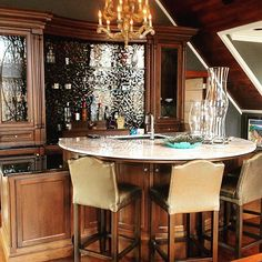 We can't think of a better place to unwind on a Friday at 5:00 than this solid walnut Martini Bar. With a circular center serving island with lighted onyx countertop, curved floating glass shelves, embellished curved crown mouldings and curved glass tile; it's all the right curves in all the right places. #werebringingFridayback #tgif #martinibar #unwindinstyle #bentonparkerdesign #duquettecabinetry