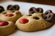 Easy! I bet that all you have to do is bake a simple suger cookie make a hole at the bottum of it, and use red m&ms as the nose, and for the eyes, chocolate m&ms and then chocolate pretzels from the antleers.