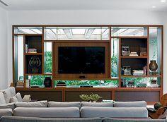 Home theater | A TV e os nichos são encaixados na esquadria de madeira com perfis de aço, feita mais grossa para passarem os fios da instalação elétrica dos aparelhos. A marcenaria, da Madeartte, e os sofás, da Álvaro Estofados, têm desenho dos arquitetos