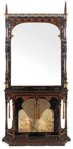 CARLO BUGATTI (1856-1940) & EUGENIO QUARTI (1867-1929) spectaculaire console orientaliste structure en bois noirci, marqueterie et colonnettes, terrasse et plateau rectangulaires à pans coupés, partie inférieure à décor, sur parchemin, d'un paysage aux ibis, plateau en bois noirci, ceinture animée de sequins, d'une tablette suspendue et de décor de passementeries. Le grand miroir est bordé de colonnettes et présente un fronton en marqueterie et découpes animées de balustres, sequins et…