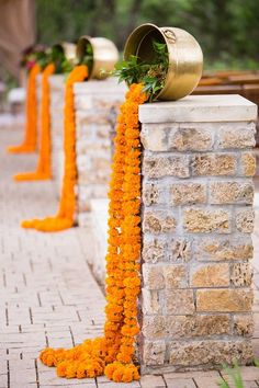 Marigold waterfall Indian wedding aisle decor with brass accents