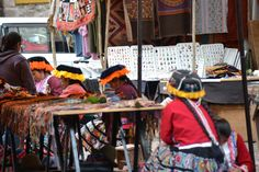 Peruvian girls working on items to sell in the Pisac, Peru marketplace