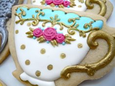 Beautiful decorated teacup sugar cookies with pink roses, trimmed in gold.