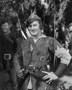The Adventures of Robin Hood (1938) Medium shot of Errol Flynn as Robin Hood (Sir Robin of Locksley), Alan Hale as Little John amidst merry men in background.