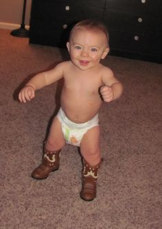 Wearing his Daddy's cowboy boots!