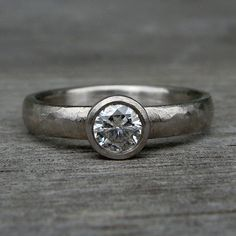 This sweetly simple ring showcases a lovely Forever One G-H-I moissanite (4.5mm; about equal in size to a 0.33 carat diamond) set in a handmade tapered bezel on a 3mm wide x 1.5mm thick comfort-fit band. All of the metal used in the construction of this ring is 950 palladium from recycled sources, and has been given a hand textured finish (though I would also be happy to give yours a polished finish if you prefer). 950 Palladium is 95% pure palladium (palladium is a noble metal in the…