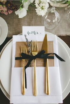 wedding place setting with gold utensils and sprig of lavender wrapped with black ribbon