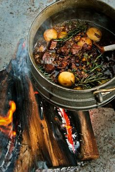 POTJIEKOS (direct translation: pot food) Slow cooked stew in a black cast iron pot a fire.