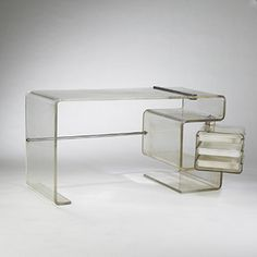 desk USA acrylic, stainless steel w x d x 30 h inches.This desk features a swiveling drawer case containing three sliding drawers.