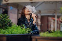 Задумчивый женщина курить на улице Бесплатные Фотографии