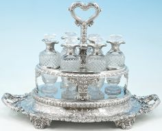 A GEORGE III SILVER CRUET FROM THE SUTTON SERVICE MARK OF PHILIP RUNDELL, LONDON, 1819, RETAILED BY RUNDELL, BRIDGE AND RUNDELL  Shaped oval and on four fruiting grapevine feet, overall chased with foliage scrolls and applied twice with a coat-of-arms, with an overhead leaf-capped handle and supports for the six silver-mounted cut glass bottles, stoppers lacking, marked underneath, on handle and bottles,