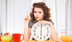 Brunette Holding a Clock and Waiting to Eat