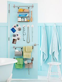 Innovative storage solutions for the back of the bathroom door.  Using towel hanging bars for versatile storage.