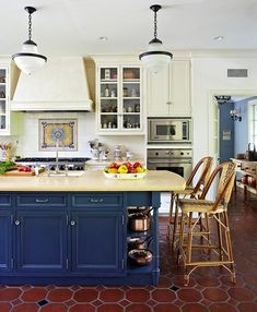 White walls and white painted cabinets recede against the rich navy blue painted surface of a kitchen island topped with creamy yellow marble. An 18th-century Portuguese tile mural installed above the range draws the eye, while a terra-cotta tile floor peppered with blue diamond-shaped tiles defines the space.