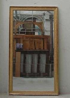 Antique neoclassical gilded mirror with its original mercury mirror.
