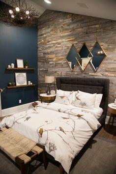 Une chambre à coucher masculine avec lit au sol, mur de briques et aux couleurs sombres