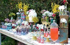 Apoiados em caixas, os vasos com flores e fitas ganham diferentes alturas e enfeitam a mesa com todas as bebidas e comidas em porções individuais