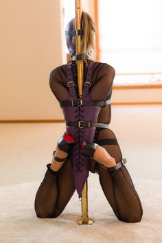 Mina is wearing a mesh catsuit by Noir Handmade, she is bound up against a brass pole while tightly laced in her purple lambskin Gwendoline Hood and Purple laced Armbinder. She is forced up onto her knees and a number of belts is added to hold her in...